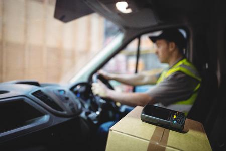 pilote de livraison van de conduire avec des colis sur le siège entrepôt extérieur