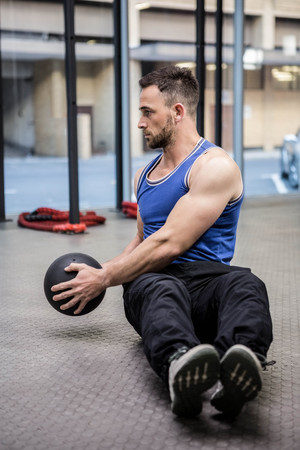 Muscular man training with exercise ball at the crossfit gym