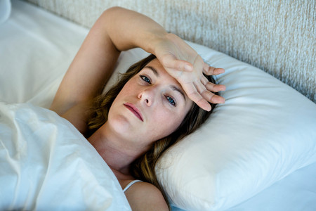 desolaci�n: depressed brunette wwoman lying in bed with her hand across her forehead