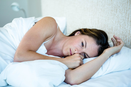 lonesomeness: tired woman lying in her bedroom on her bed Stock Photo