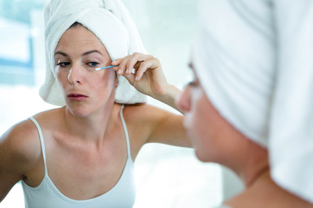 cotton bud: woman wearing a hair towel using a cotton bud to fix her mascara Stock Photo