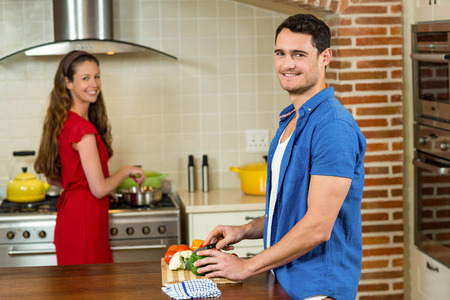 home cooking: Man chopping vegetables and woman cooking on stove in kitchen at home