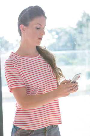 mouthed: angry woman standing inside a window reading her mobile phone