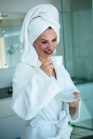 bath gown: woman wearing a dressing gown and a towel on her head is smiling at the camera