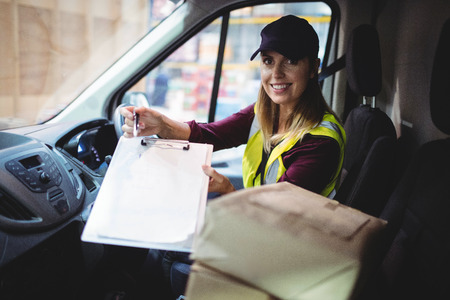 loading bay: Delivery woman holding clipboard to camera with parcels on seat Stock Photo