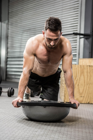 planking: Shirtless man planking on bosu ball at the crossfit gym
