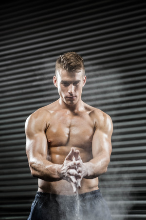 manos aplaudiendo: Hombre sin camisa, con las manos aplaudiendo talco en el gimnasio CrossFit Foto de archivo