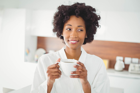 bath robe: Pretty woman in bath robe drinking coffee in the kitchen at home