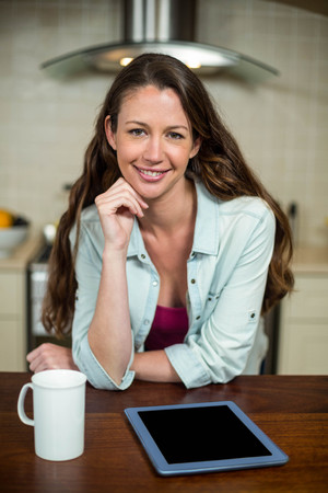 technolgy: Portrait of young woman in kitchen with coffee mug and digital tablet on worktop Stock Photo