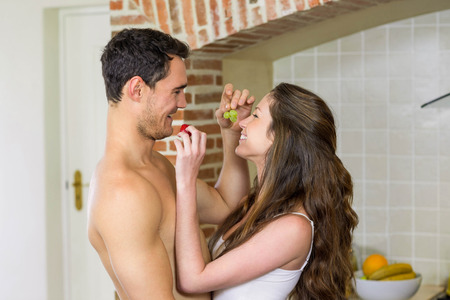 each: Young couple feeding fruits to each other in kitchen