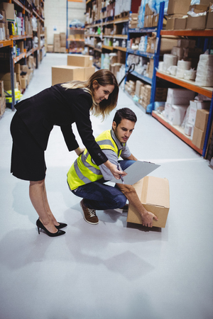 Young worker: Manager showing clipboard to worker in warehouse