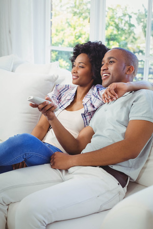 changing channel: Happy couple watching tv on the sofa Stock Photo