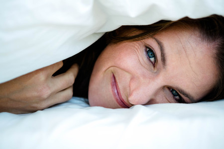 pulled over: smiling woman with a duvet pulled over her head