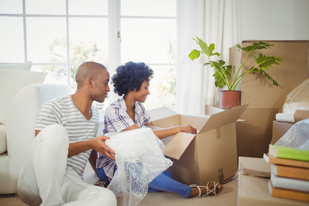 put away: Happy couple opening boxes in the living room Stock Photo