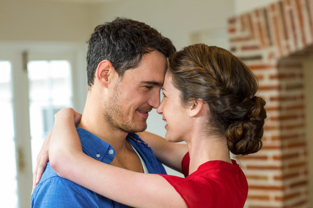 each other: Close-up of romantic couple standing face to face and embracing each other in kitchen