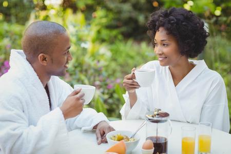 breakfast garden: Happy couple taking breakfast in the garden at home