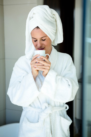 dressing gown: woman in a dressing gown drinking a cup of coffee