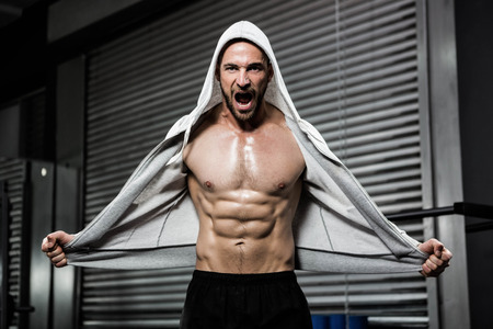 jumper: Shirtless man with grey jumper shouting at the crossfit gym Stock Photo