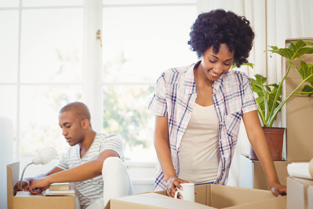 moving box: Happy couple opening boxes in the living room Stock Photo