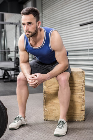 wooden block: Muscular man sitting on wooden block at the crossfit gym