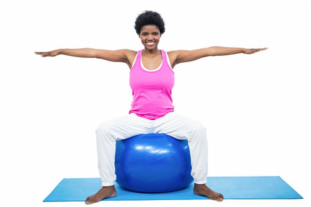 prenatal care: Pregnant woman on exercise ball on white background