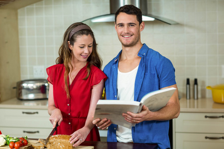 checking ingredients: Woman cutting loaf of bread while man checking the recipe book in kitchen at home Stock Photo