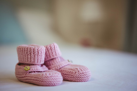 View of baby shoes on a bed at home