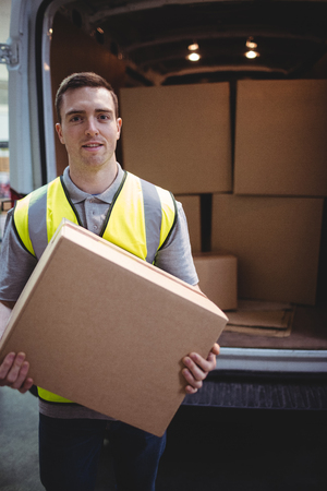 loading bay: Delivery driver smiling at camera by his van holding parcel outside the warehouse