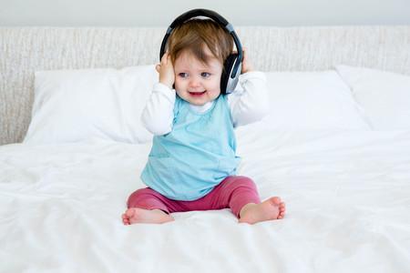 Sonriente bebé sentado en una cama jugando con auriculares Foto de archivo