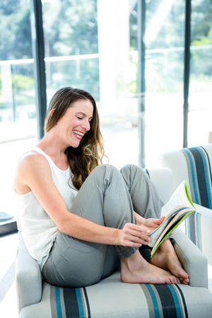 woman couch: smiling woman sitting on a couch, reading a book