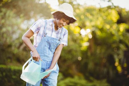 watering plants: Smiling woman in the garden watering plants