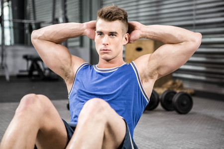sit up: Muscular man doing abdominal crunches at the crossfit gym Stock Photo