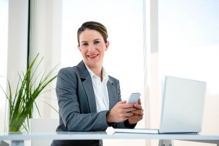 at her desk: smiling business woman, at her desk, on her mobile phone