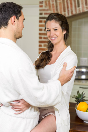 each other: Romantic young couple in bathrobe cuddling each other in kitchen Stock Photo