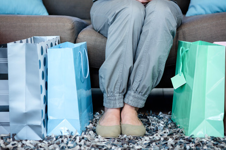 gift bags: Womans feet surrounded by gift bags as she sits on the couch