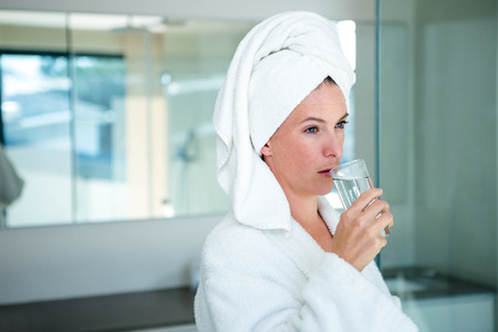 dressing gown: woman in a dressing gown with a towel on her head drinking a glass of water