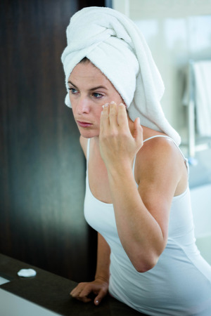 moisturiser: woman wearing a towel on her hair,applying face cream in the mirror