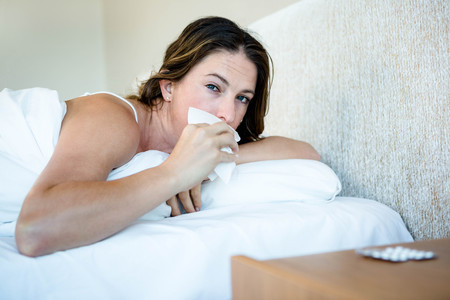wiping: Sick woman lying in her bed wiping her nose Stock Photo