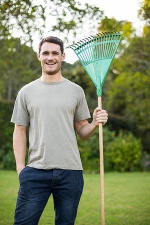 weekend activity: Portrait of young man standing with a gardening rake in garden Stock Photo