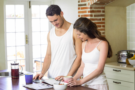 personal organizer: Young couple looking their personal organizer while having breakfast in kitchen