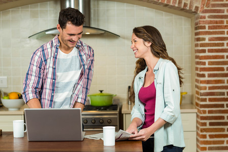 worktop: Man using laptop and woman reading newspaper on kitchen worktop Stock Photo