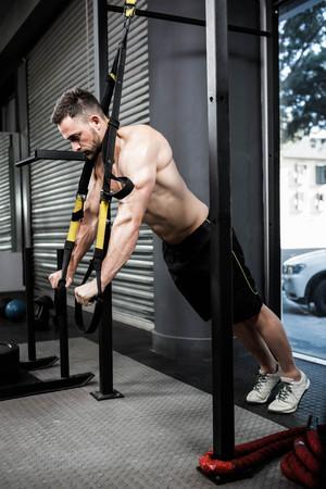 hang body: Shirtless man hanging at the rope at the crossfit gym