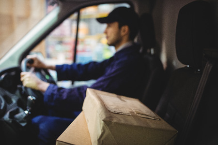 loading bay: Delivery driver driving van with parcels on seat outside warehouse