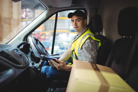 loading bay: Delivery driver using tablet in van with parcels on seat outside warehouse