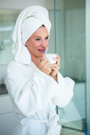 bath gown: woman wearing a dressing gown and a towel on her head is smiling at the camera with a cup and saucer in her hand