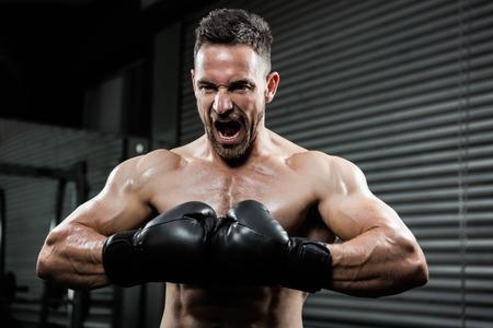 hombre deportista: hombre sin camisa enojado con los guantes del boxe gritando en el gimnasio CrossFit