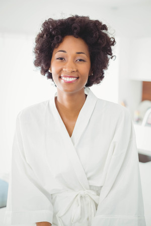bath gown: Pretty woman in bath robe smiling at the camera in the kitchen at home