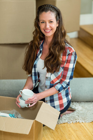 unpacking: Portrait of young woman unpacking carton boxes in new house Stock Photo