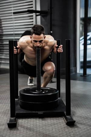 man pushing: Shirtless man pushing heavy weights at the crossfit gym