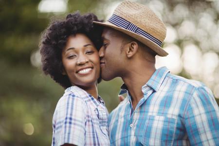 cheek: Smiling man kissing her girlfriends cheek in the garden